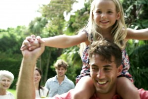 unused - father with daughter on his shoulders and famly in background