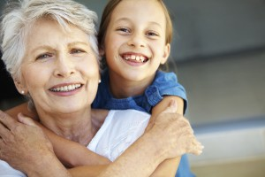 Closeup of a grandmother being embraced by her cute granddaughter - Copyspace