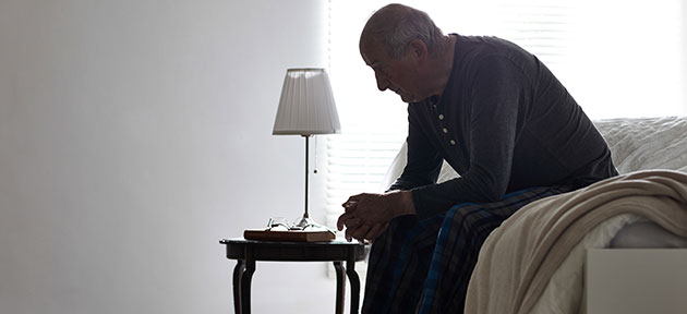 Illustrating the impacts of elder abuse, this image shows an elderly man, sitting on the edge of his bed, head stooped in thought.